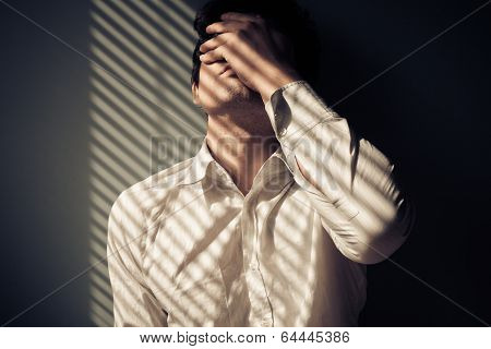 Man By Window With Shadows From Blinds