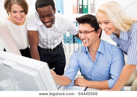 Happy business people gathered around laptop looking at monitor in the office