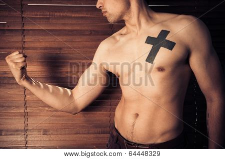 Young Man Flexing His Muscles By Window