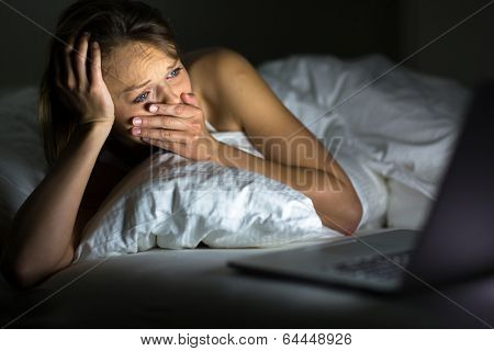 Pretty young woman watching something awful/sad on her laptop in bed
