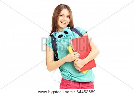 Smiling female with schoolbag and headphones looking at camera and leaning against a wall