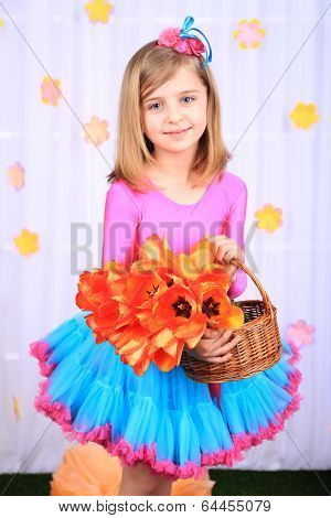 Beautiful small girl in petty skirt holding basket with flowers on decorative background