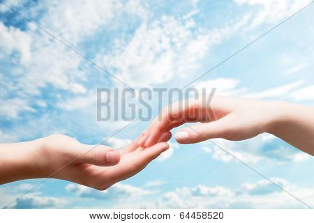 Man and woman hands touch in gentle, soft way on blue sunny sky. Concepts of connection, hope, faith, help, love.