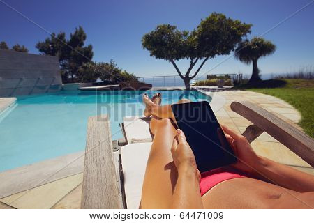 Relaxed Woman Using Digital Tablet By Poolside