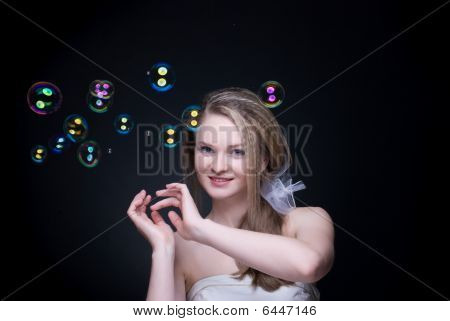 Closeup Portrait Of Blond Girl With Soap Bubbles On Black