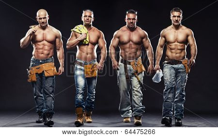 Group Of Young Handsome Builder Posing, On Dark Background