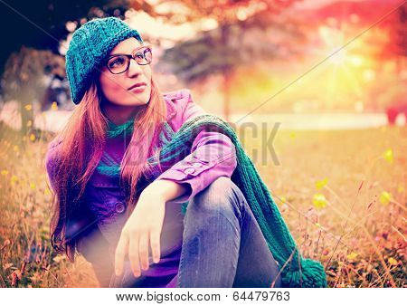 girl sitting in a meadow in sunset