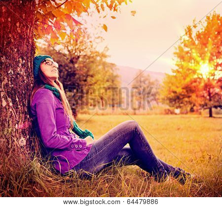 girl sitting under a tree in sunset