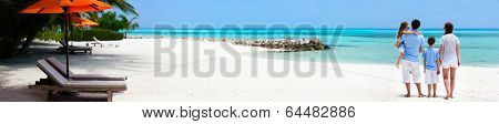 Back view of a beautiful family on a beach during summer vacation. Wide panorama, perfect for banners