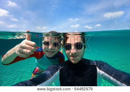Split above and underwater photo of father and son swimming