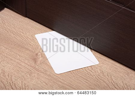 white envelope with message slipped under wooden door.
