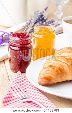 Raspberry and orange jam with croissant.