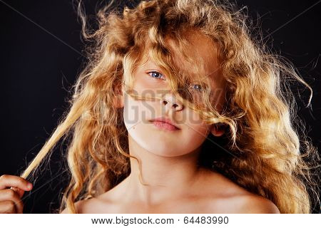 Portrait of little girl with windy hair. Fashion photo