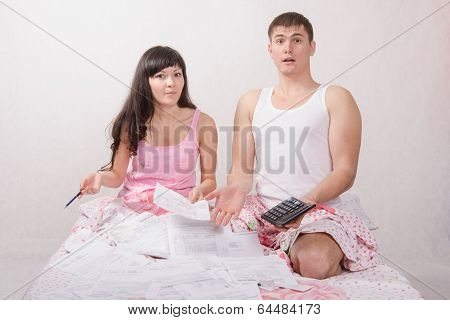 Young Couple Sitting In Bed, Shocked By Amount Of Accounts