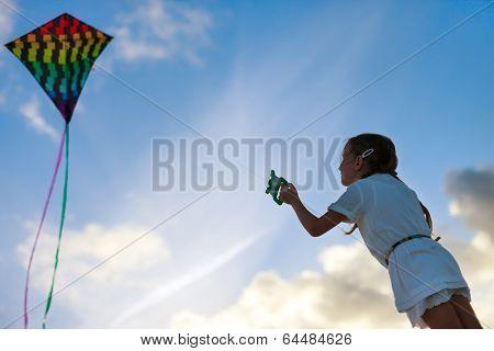 Little girl flying a kite at sunset