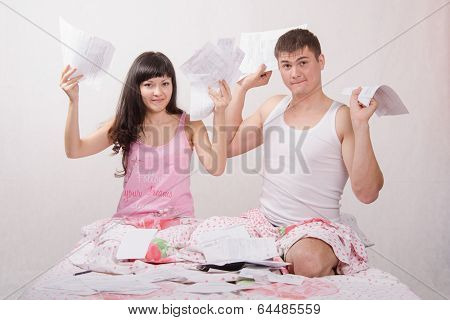 Young Family With Bills For Apartment Sits In Bed