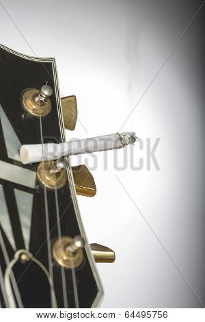 Close Up Of A Guitar Headstock With Burning Cigarette Sticking Under One String