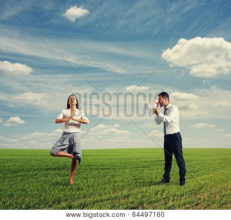 angry young businesswoman and calm yoga woman on the field