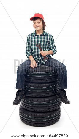 Young Mechanic Boy Sitting On New Car Tires