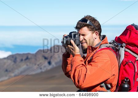 Nature photographer taking pictures outdoors on hiking trip in the mountains