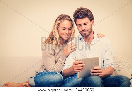 Happy young couple at home using digital tablet