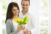 picture of amor  - Amorous couple together with beautiful  bouquet of tulips - JPG