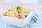 stock photo of chinese parsley  - Tasty instant noodles with vegetables in bowl on table close - JPG
