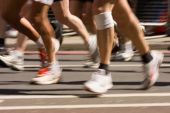 stock photo of sports injury  - A low perspective of runners in a marathon - JPG
