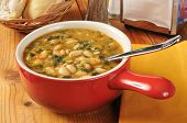 stock photo of kale  - A bowl of healthy kale and white bean soup with dinner rolls - JPG