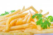 stock photo of potato chips  - french fries in close up with parsley on top; crispy deep-fried golden potato chips; roasted potatoes french fried chips