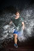 foto of sprinter  - Sprinter rennt durch eine Wasserwand mit viel Spray - JPG