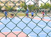 stock photo of chain link fence  - Seamless chain link fence with basketball court background - JPG