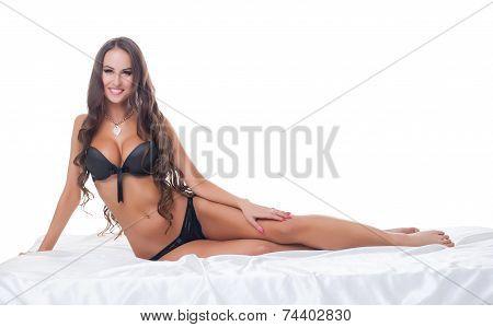 Image of smiling lingerie model posing in bed