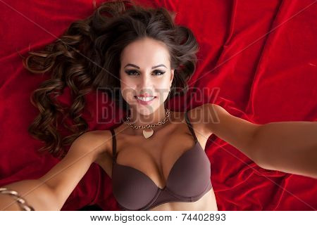 Sexy model takes selfie while lying on satin sheet