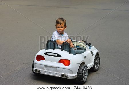 Kid In The Park Riding A Toy Car