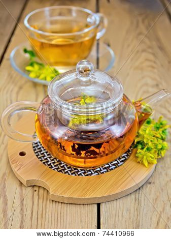 Herbal tea from tutsan in glass teapot on stand with cup