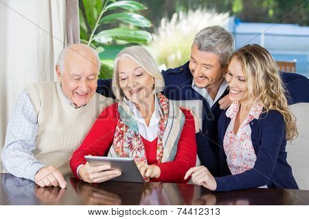 Happy grandchildren looking at grandparents using digital tablet in nursing home