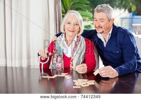 Portrait of grandmother holding walking stick while playing dominoes with grandson at nursing home