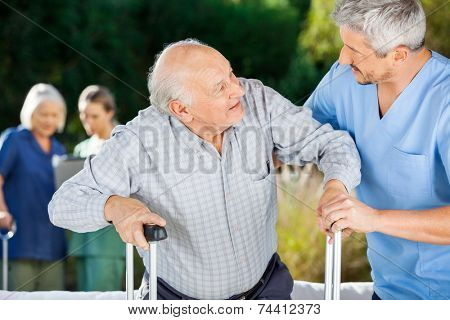 Male and female nurses helping senior people in nursing home