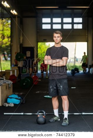 Full length portrait of fit man with arms crossed standing at health club