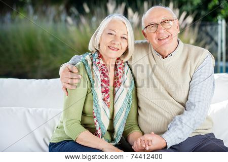 Portrait of happy senior man sitting with arm around woman on couch at nursing home porch