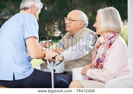 Male doctor measuring blood pressure of senior man while woman looking at them at nursing home