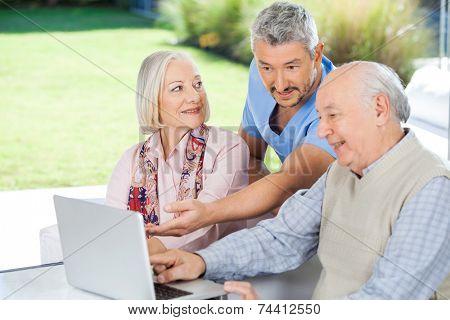 Male caretaker showing something to senior couple on laptop at nursing home