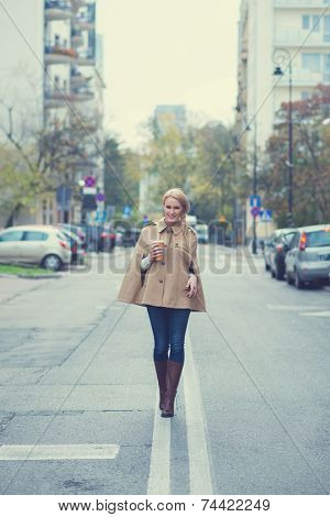 Young woman walking down the center line in an urban road carrying a cup of takeaway coffee