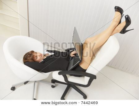 Woman Funny Located In Two Office Chairs With Laptop