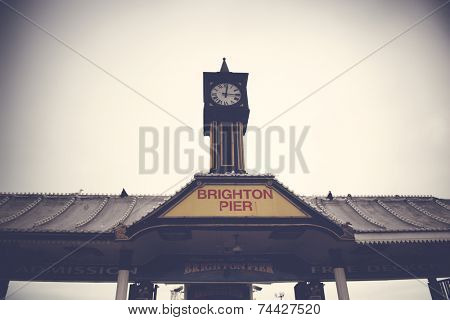 Exterior low angle view of the historical clocktower and sign for Brighton Pier at brighton, East Sussex, UK