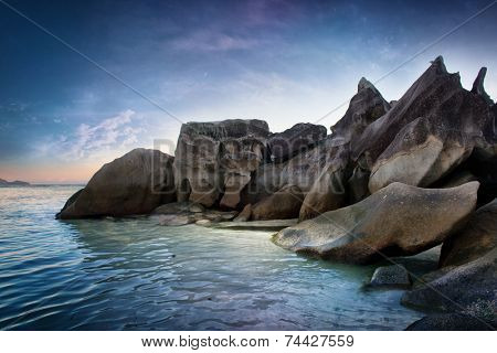 Attractive Spot of Huge Rocks at Seychelles at the Side of Beautiful Blue Water Sea. Captured on Gradient Blue Sky Above.