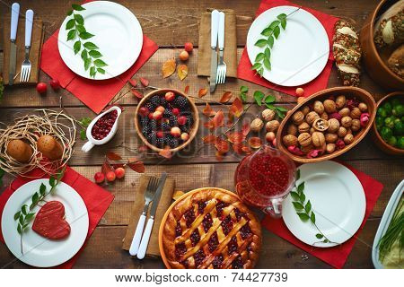 Fresh rennets, walnuts, pastry, jam, fruit drink and berries on wooden table