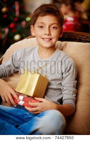 Portrait of handsome boy with giftboxes looking at camera