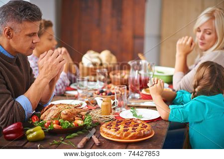 Portrait of modern family of four sitting at festive table and praying